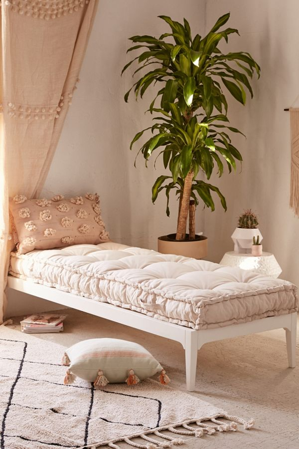 daybed with white bed platform, white fluffy cushion, pillows, plant, white side table, white rug