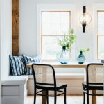 Dining Nook, White Built In Bench, Square Wooden Table, Black Chair With Rattan Seating And Back, Windows, Sconces