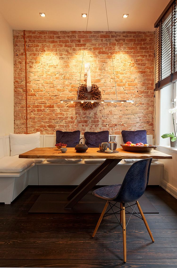 dining nook, white corner bench with white cushion, rectangular wooden table with slanting legs, black miidcentury chair, open brick wall, pendant