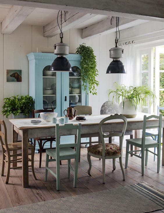 dining room, wooden floor, long wooden table, different desgined wooden chairs, pendant, blue wooden cupboard with glass door, wooden beam, window