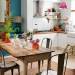 Dining Table Set, Brown Rug, Wooden Long Table, Metal Chairs, White Wall, White Upper And Bottom Cabinet, White Wall, Pink Pendant, Blue Wall With Large Mirror