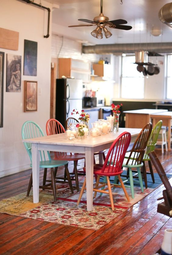 dining table set, white long table, colorful wooden chairs, wooden floor, colorful rug, white wall, kitchen on the side, ceiling fan