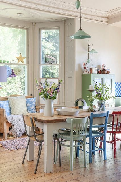 dining table set, wooden table, colorful wooden chairs, wooden floor, white wall, wooden sofa near the window with pillows, green pendant, green wooden cupboard