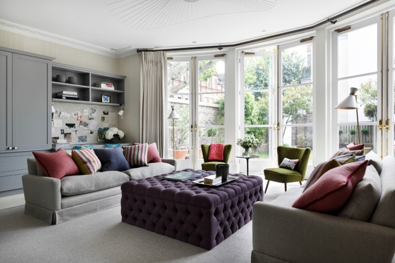 drapery pole glass doors floor lamps purple tuted ottoman grey sofas colorful pillows drapes grey cabinets green chairs