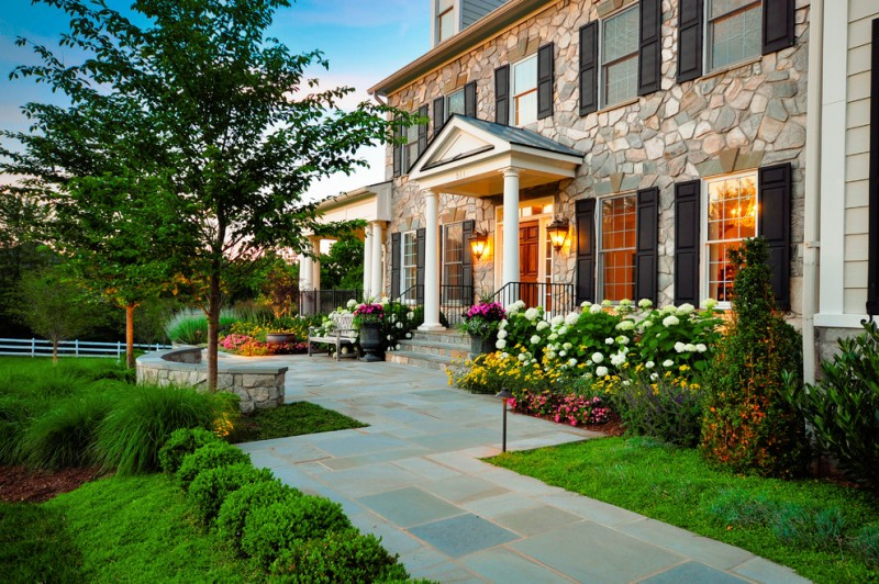 exterior landscaping trees grass green balls mosaic pavers stone walls wooden doors bench glass windows wall sconces flowers stairs