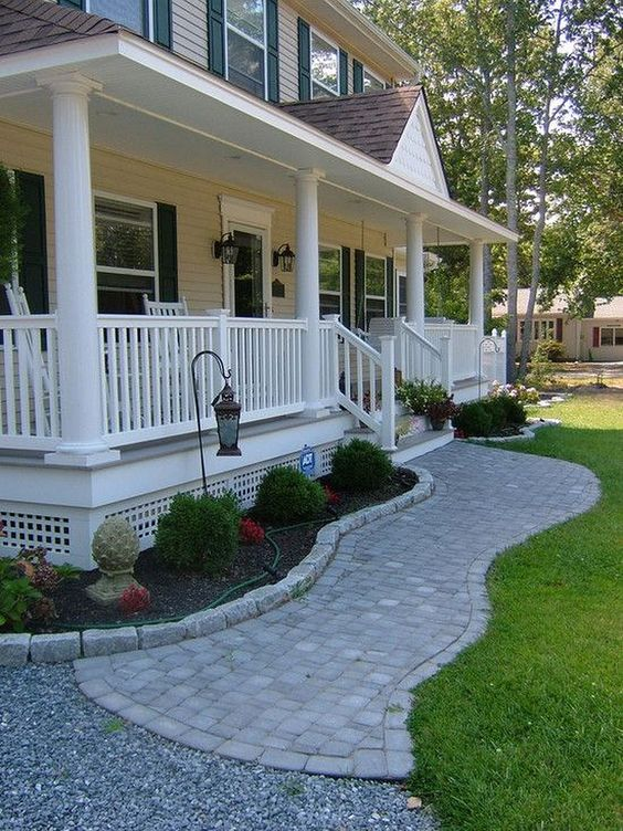 farmhouse front, white wooden rail and posts, grass, bushes, brick path