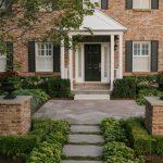Flagstone Walkway Design Ideas Herringbone Stone Black Flower Pot White Pillars White Windows Brick House Wall Sconce Black Door