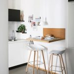 Floating Wooden Table, Wooden Stools With White Seating, White Wall, White Cabinet, Black Upper Cabinet, White Pendant
