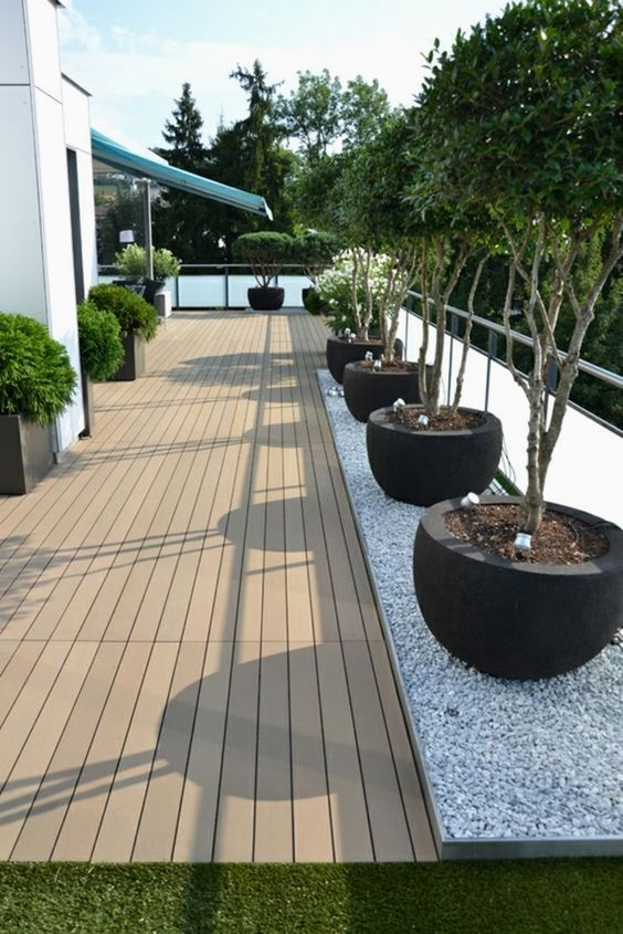 front porch, wooden floor, grey marble floor, plants on black round pots, plants on square pots, grass
