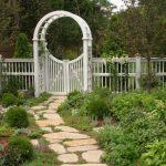 Garden Arbor Ideas Stone Walk Grass Flowers Mini Garden White Wooden Fence White Wooden Gate White Wooden Arbor