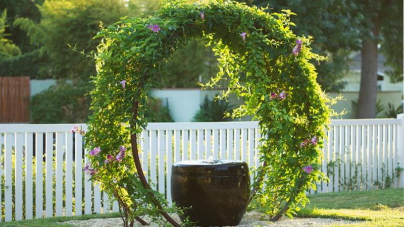 garden arbor ideas white wooden low garden fence black stool stainless steel wire grass flowers rocky space
