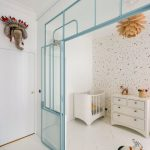 Glass Partition To White Nursery, Blue Frame, White Wooden Floor, White Cabinet, White Crib, Orange Pendant