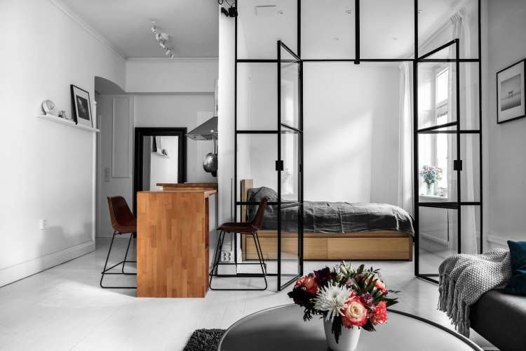 glass partition with black metal frame separating bedroom, wooden bed platform, wooden table, red stool, round coffee table