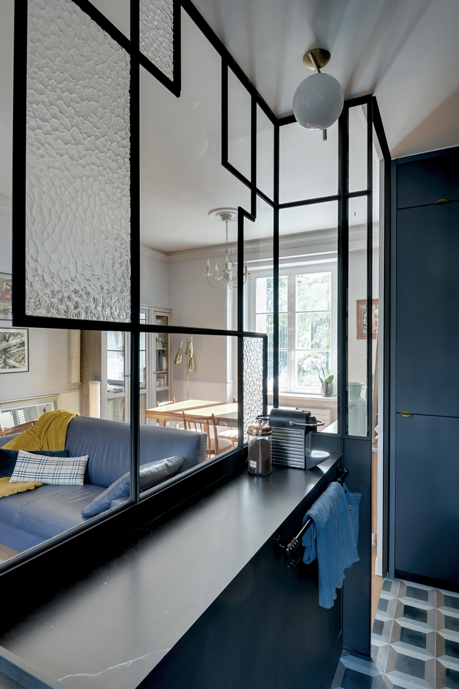 glass partition with black metal lines pattern, white ceiling lamp, towel holder