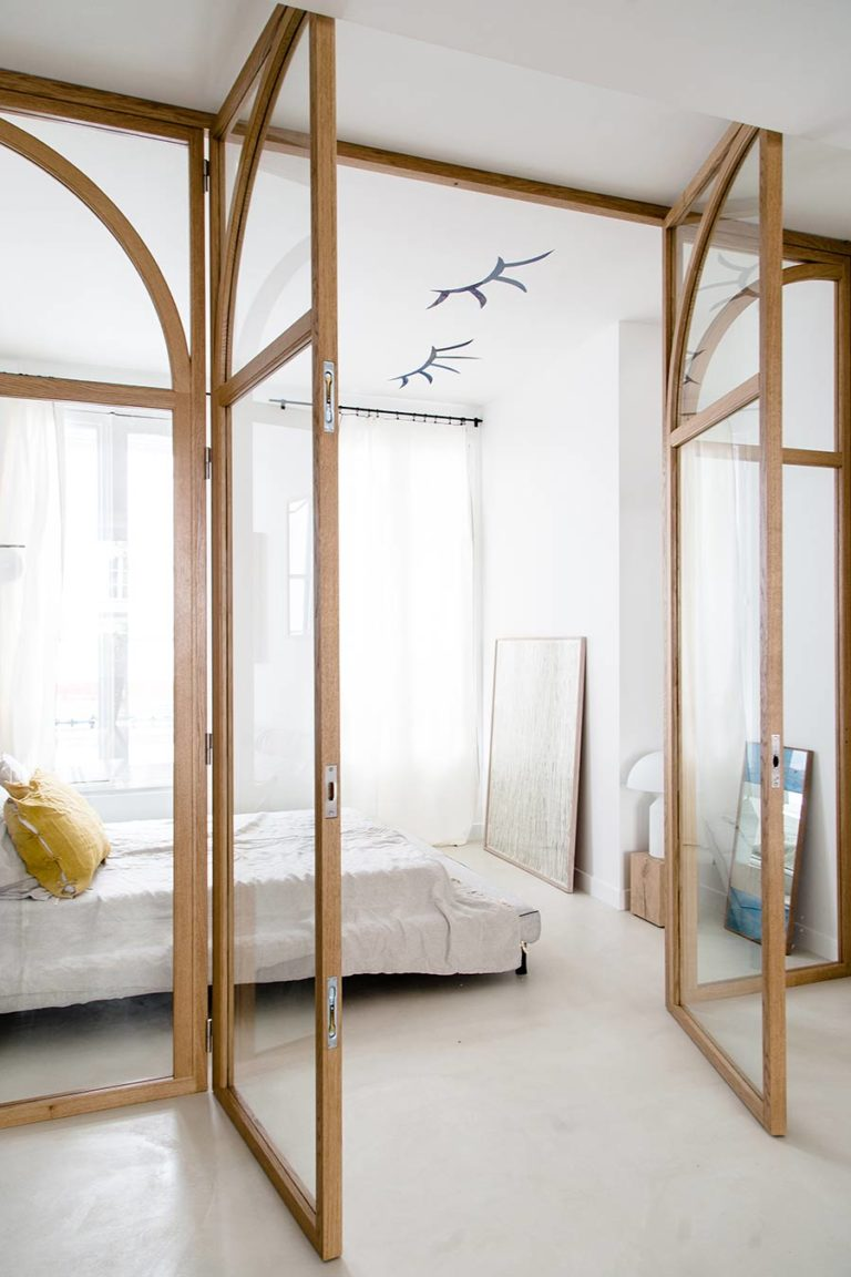 glass partition with brown frame, half ellipse pattern on top, separating bedroom