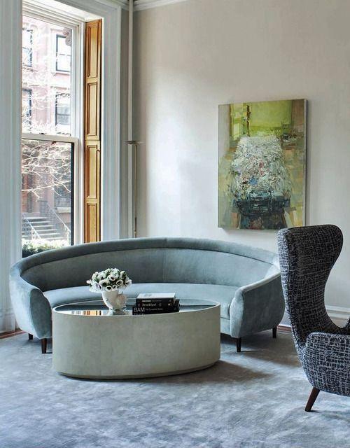 green cornered curvy sofa, round coffee table with glass top, blue rug, grey chair, beige wall, windows