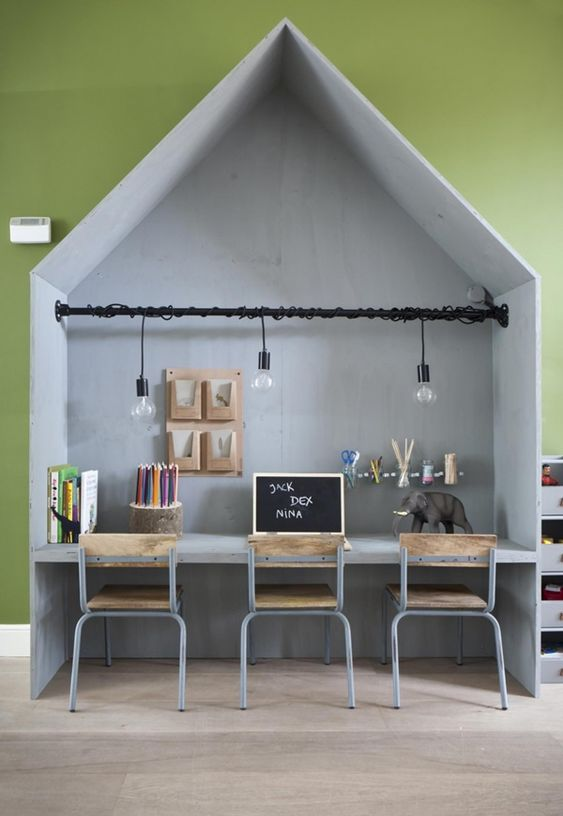 grey house box for study with table inside, black rail for pendants, low grey metal chairs