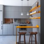 Grey Kitchen With Floor Wall Cabinet In Grey, Yellow Floating Shelves And Bar Table, Wooden Stools, Bulb Pendants