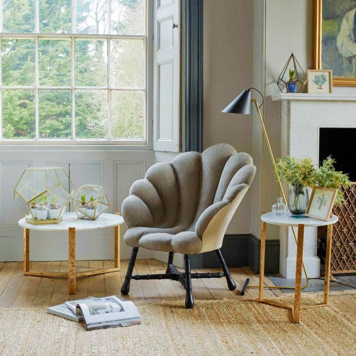 grey shell chair with black legs, wooden floor, rattan rug, wooden side table and coffee table with white marble top, windows, white wall, black modern floor lamp