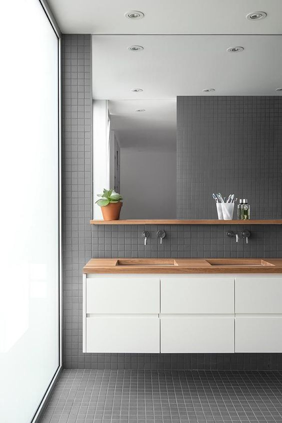 grey square tiles on wall, floor, white floating vanity with wooden top, large mirror, wooden floating shelves