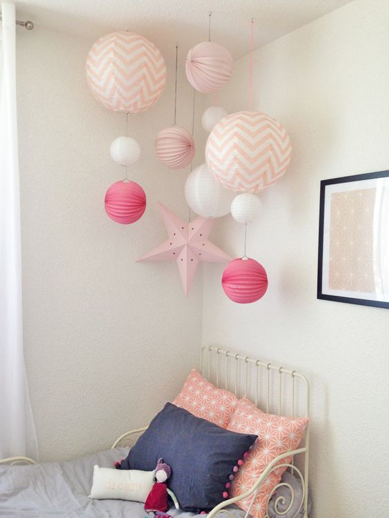 kid bedroom, white metal bed platform, grey bedding, white wall, pink lanterns on the corner ceiling
