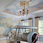 Kids Bedroom With Beige Rug, Blue World Map Art Wall, Cloud Statement Ceiling, Chandelier, Plane Shaped Bed