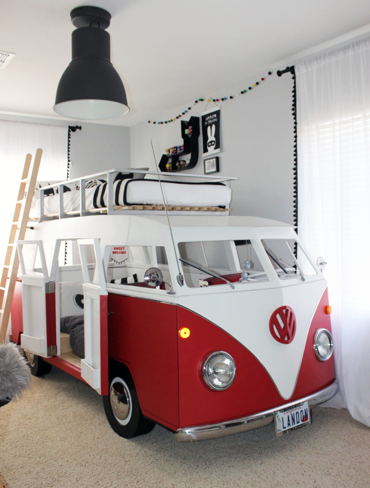 kids bedroom with beige rug, white red bus with bed on top, white wall, black ceiling lamp