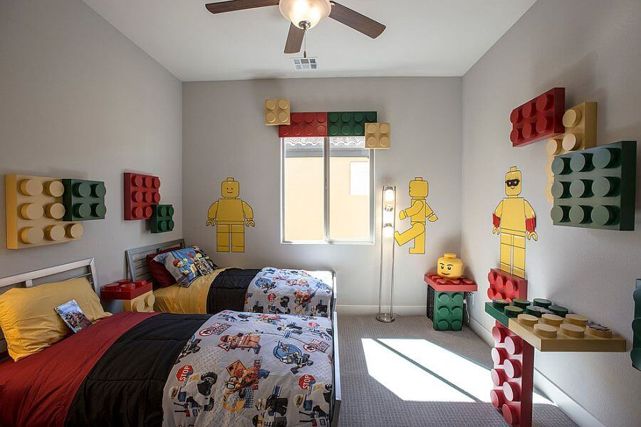 kids bedroom with grey floor, grey wall, lego details on above the bed headboard, window, table, floating table, bed with colorful bedding, ceiling fan