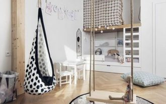 kid's bedroom with wooden floor, white wall, wooden swing, polka dot swing, white wooden kids table chair, wooden bunk bed, climbing ropes, round rug