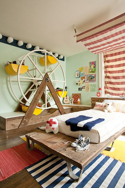 kids bedroom, wooden floor, wooden bed platform, white bedding, varied clothes rug, red striped curtain, green wall,