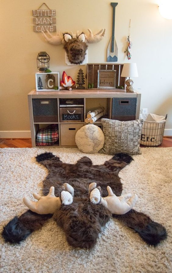 kids room with wooden floor, beige rug, animal shaped rug, wooden shelves with boxes, wall decorations
