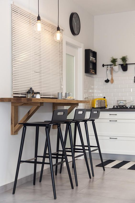 kitchen, beige floor, white wall, floating wooden table, black stools, white cabinet, white subway tiles backsplash, black rail on the wall, pendant