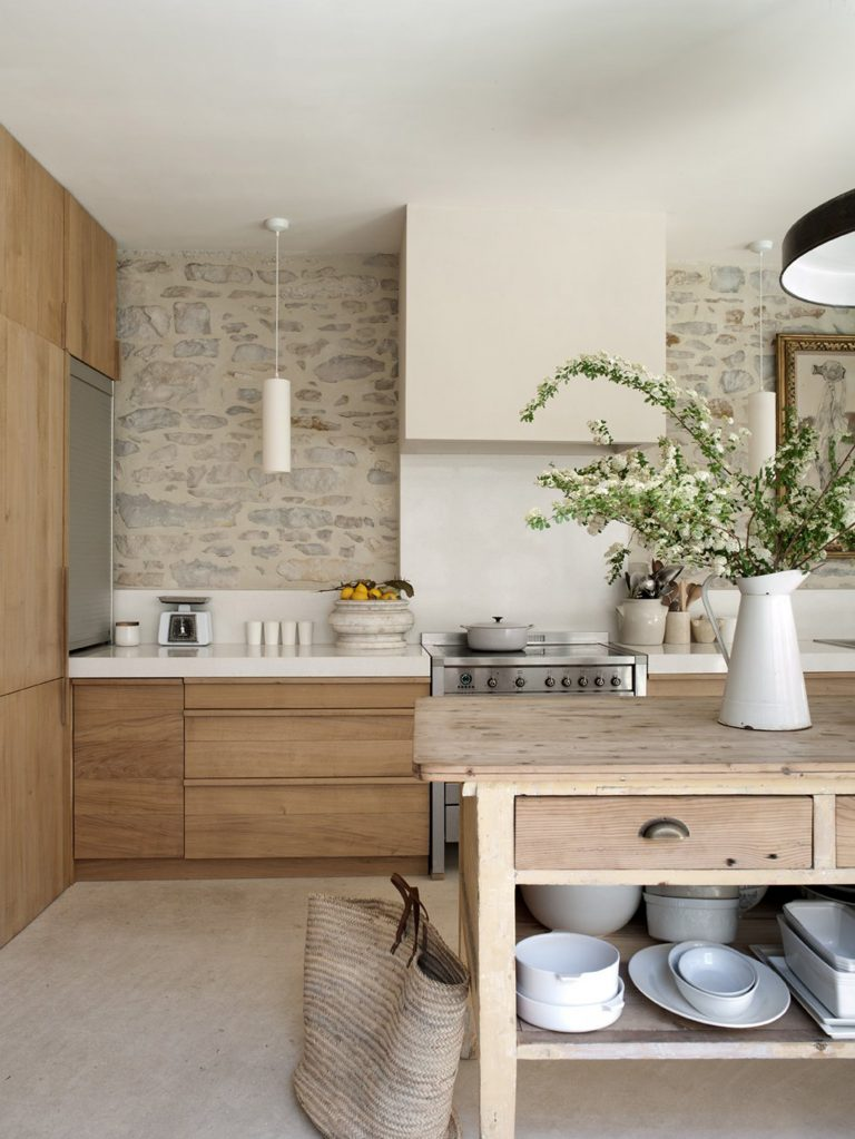 kitchen, beige floor, wooden pantries, cabinet, wooden table for island, natural stone wall, white backsplash tiles, white kitchen top