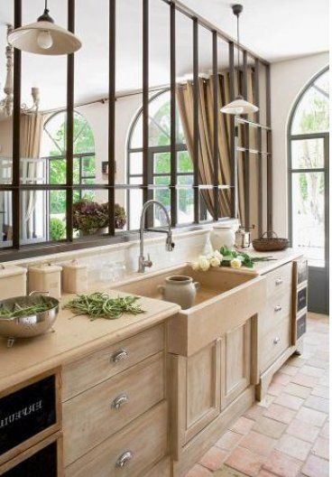 kitchen, brick floor tiles, wooden cabinet, farmhouse sink in brown, mirror wall, pendants, brown marble top