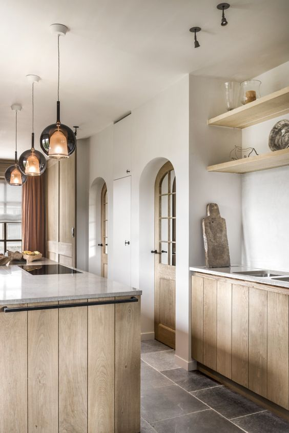 kitchen, dark floor tiles, white wall, wooden planks cabinet, marble top sith undermount sink, floating shelves, pendants