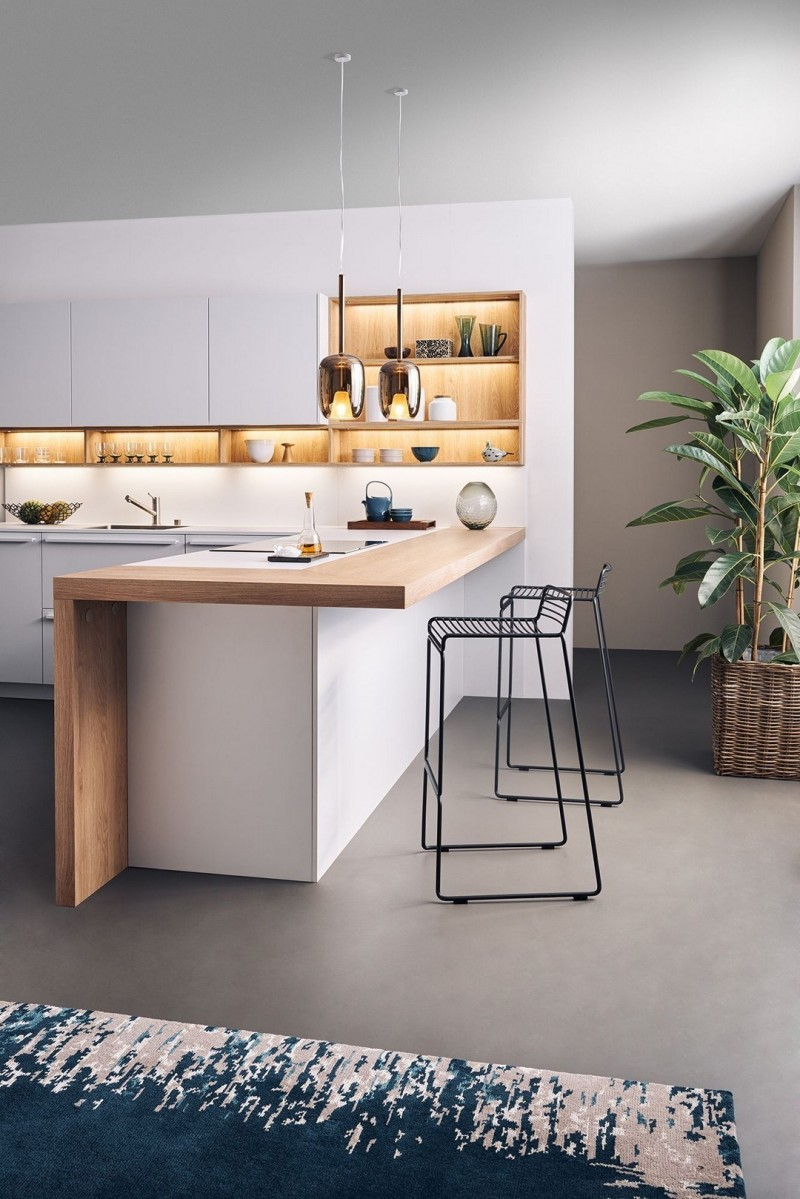 kitchen, grey floor, light grey island and kitchen table with wooden layers on top, white cabinet with shelves in the middle with LED light