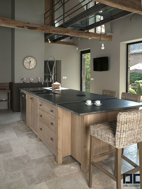 kitchen, traditional floor tiles, wooden island with cabinet, black marble top, undermount sink, rattan stools, grey wall, wooden beams
