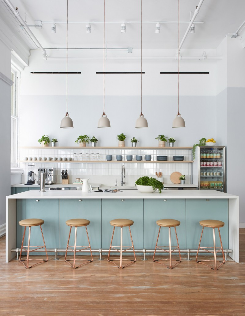 kitchen with modern island bar, white backsplash tiles, white tiles, pastel blue kitchen cabinet and island with white top, white pendants