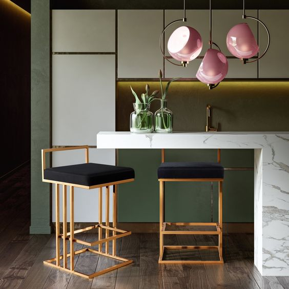 kitchen with modern island bar, white green cabinet, white marble island, golden colored stools with black seating, modern pink pendants
