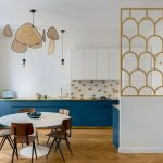 Kitchen, Wooden Chevron Floor, White Wall, White Upper Cabinet, Blue Bottom Cabinet, Golden Kitchen Top, Fish Scales Backsplash, Golden Fishscales Partition