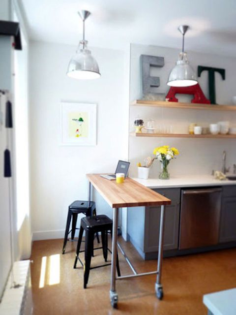 kitchen, wooden floor, grey cabinet, white wall, floating shelves, wooden table on wheels, black stools, silver pendants