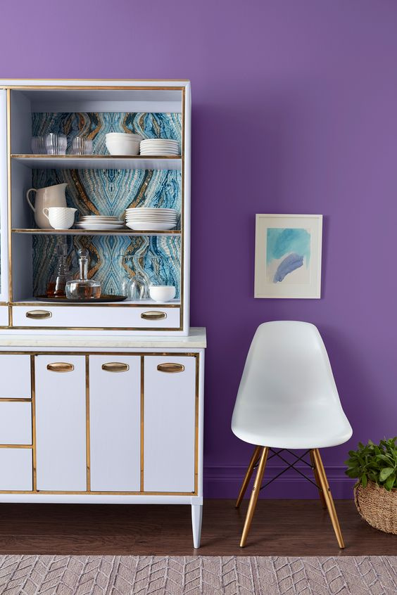 kitchen, wooden floor, rug, white cabinet with golden line, white modern chair, purple wall