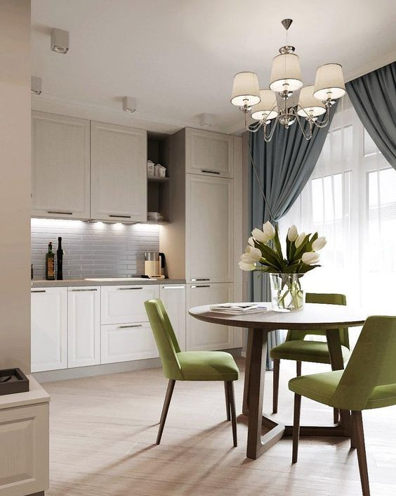kitchen, wooden floor, white cabinet upper and bottom, grey backsplash, white chandelier with cover, round wooden table, green tables