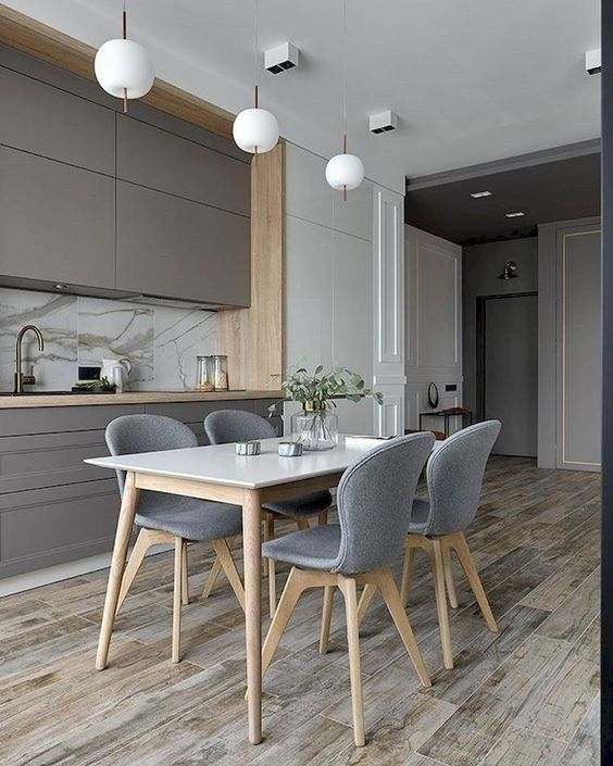 kitchen, wooden floor, white ceiling, grey upper and bottom cabinet, marble backsplash, white cupboard, white pendants, white wooden table, grey modern chairs