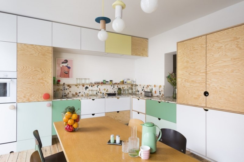 kitchen, wooden floor, white, yellow, green cabinet, wooden cabinet, terazzo backsplash, white naked pendants