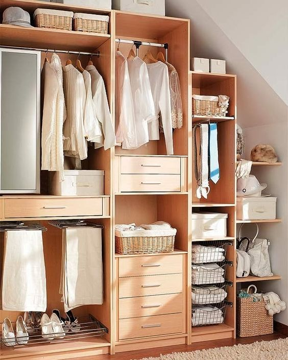 large wooden boxes without door under the sloping ceiling with rails, drawers and boxes inside the shelves