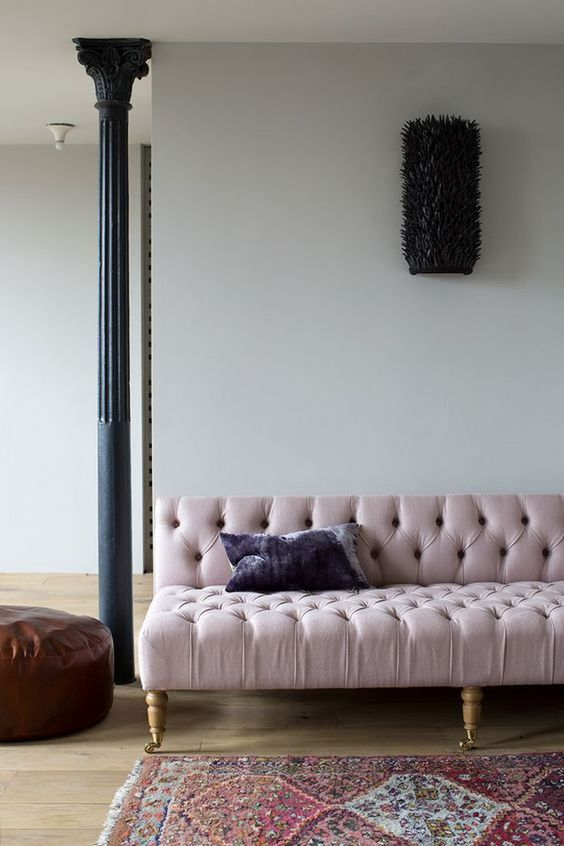 light purple tufted sofa with tufted surface in the seating adn back, wooden legs, wooden floor, moroccan rug, leather ottoman