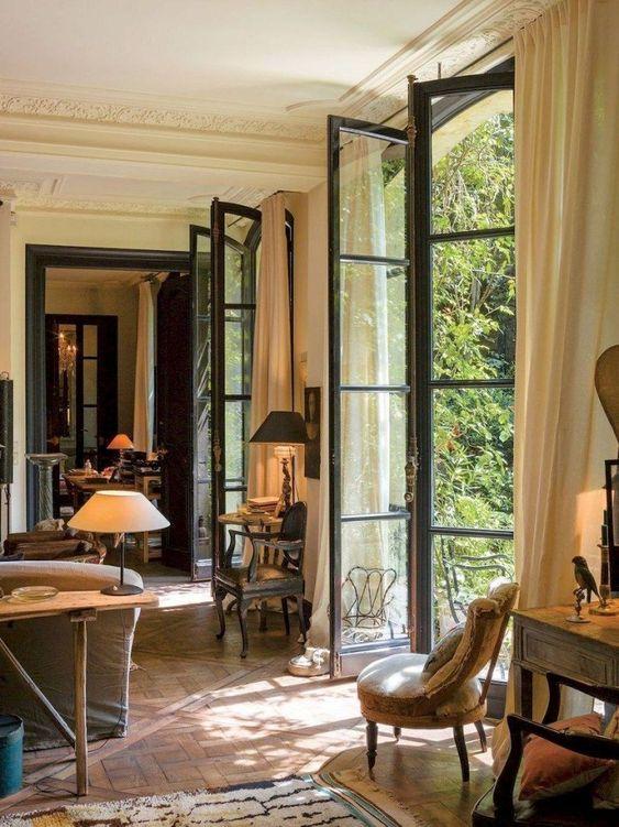 living room, basket weave flooring, white molding ceiling, tall glass door, sofa, vintage chair
