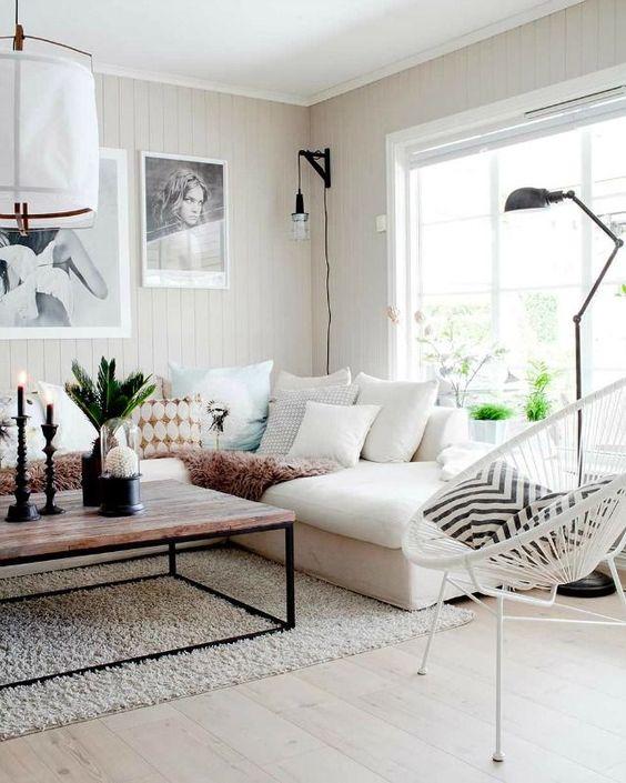 living room, light wooden floor, rug, white cornered sofa, wooden table, white rattan chair, white plank wall, black floor lamp, white paper pendant