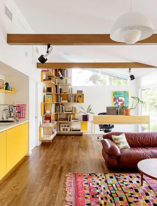 living room, open room, wooden floor, maroon leather sofa, colorful rug, cornered wooden shelves, wooden office table, black office chair, yellow cabinet, wooden beams